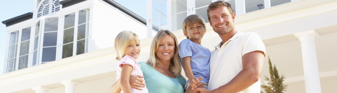 A young family with children in front of a large upscale home