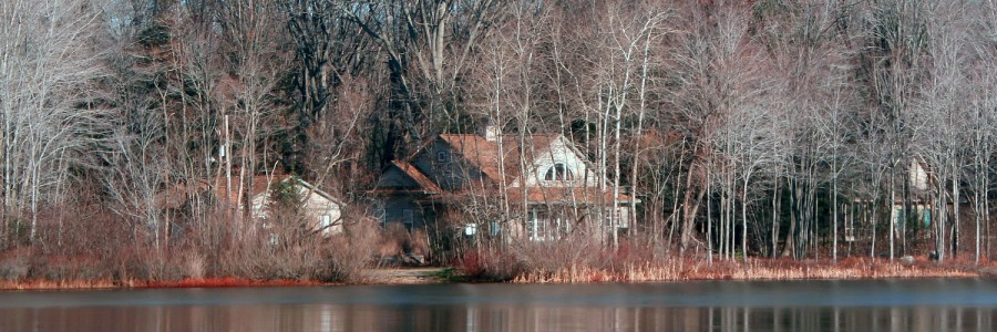 View of a large home on a wooded lake